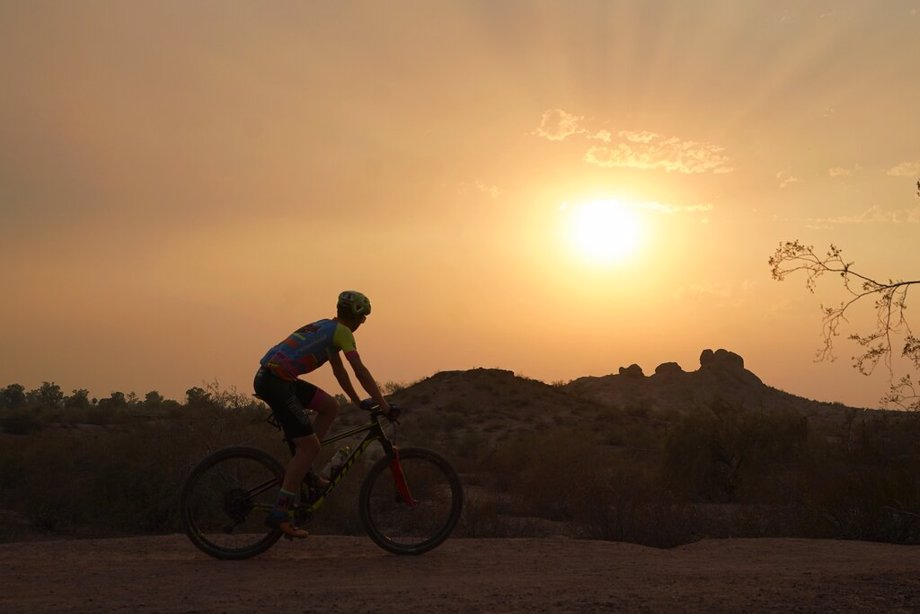 A cyclist bikes past the setting sun at Papago Park during a heatwave where temperatures hit 115-degrees in Phoenix