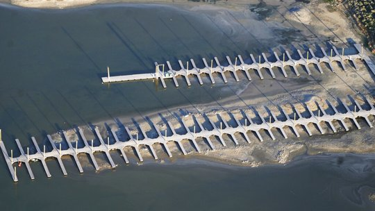 Shallow water is seen from above at a boat dock at Antelope Island, Utah