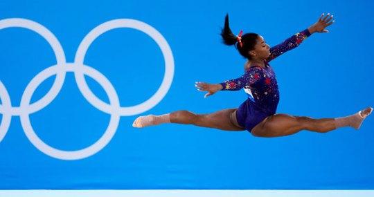 Gymnast Simone Biles mid-air in a blue leotard