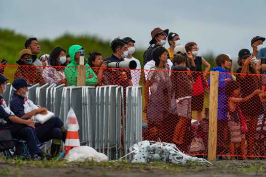 People watch Olympics from behind a security fence