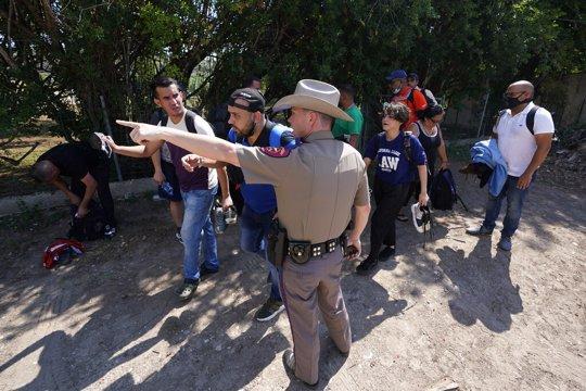Texas Trooper and Migrants at Border