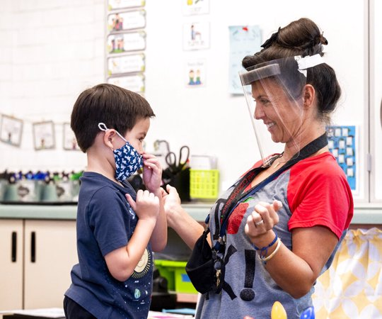 A student gets help with his mask from transitional kindergarten teacher Annette Cuccarese during the first day of classes at Tustin Ranch Elementary School in Tustin, Calif.