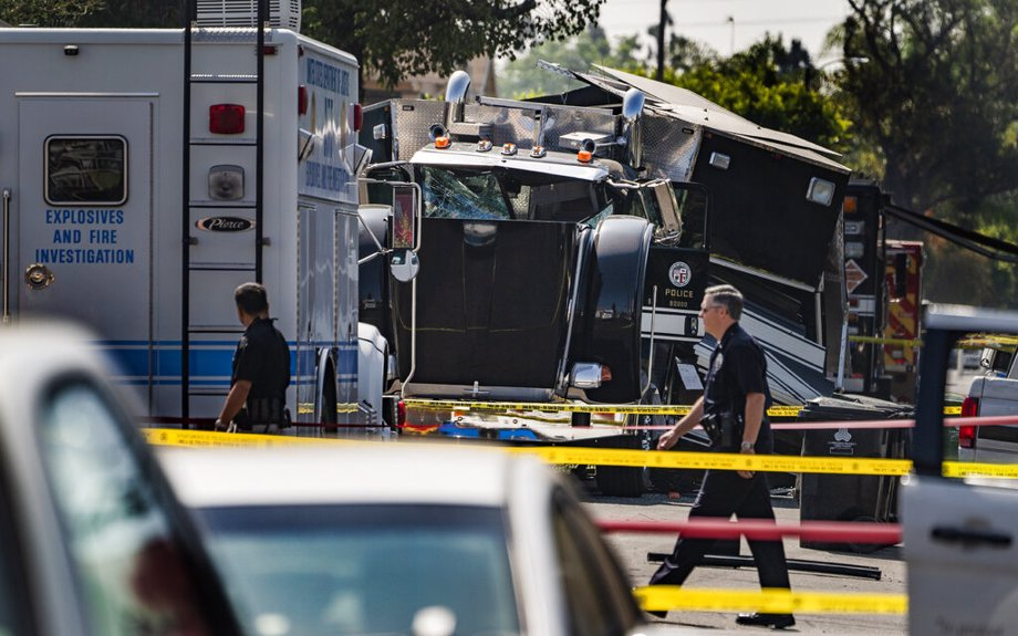 Police walk past the remains of an armored tractor trailer