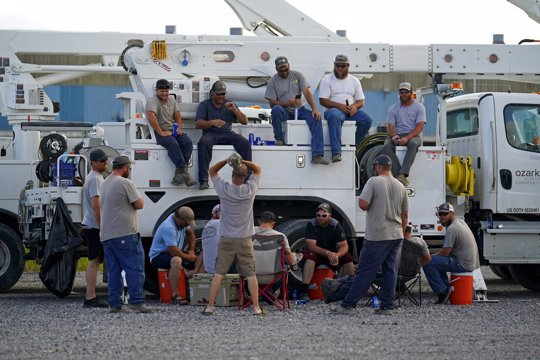 Electrical workers congregate in the evening after parking their trucks after a day's work at a tent city in Amelia, La.