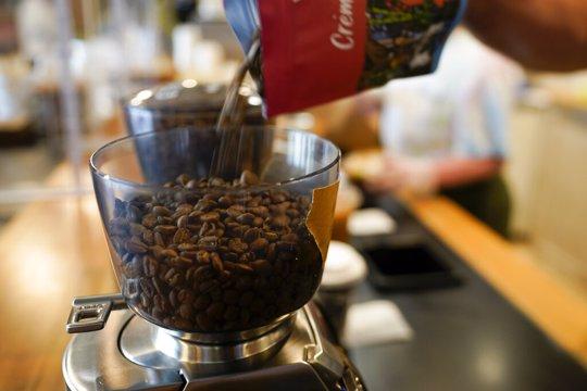 Chris Vigilante refills a coffee grinder with coffee beans at Vigilante Coffee