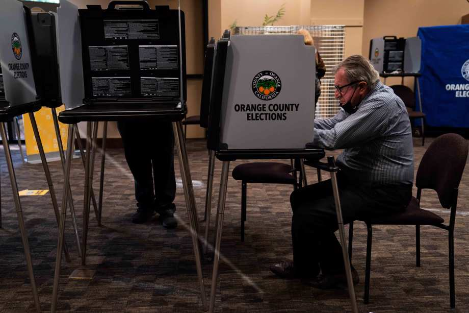 In this Sept. 14, 2021, file photo, two voters cast their ballots at a vote center, in Huntington Beach, Calif. Every registered California voter will get a ballot mailed to them in future elections under a bill signed Monday, Sept. 27, 2021, by Democratic Gov. Gavin Newsom.
