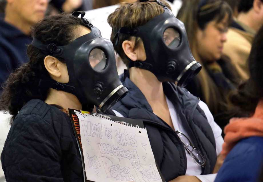 In this Jan. 16, 2016, file photo, protesters wearing gas masks, attend a hearing over a gas leak at the southern California Gas Company's Aliso Canyon Storage Facility near the Porter Ranch section of Los Angeles.