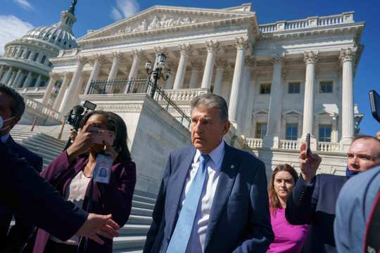 Sen. Joe Manchin, D-W.Va., a centrist Democrat vital to the fate of President Joe Biden's $3.5 trillion domestic agenda, is surrounded by reporters outside the Capitol in Washington, Wednesday, Sept. 29, 2021.