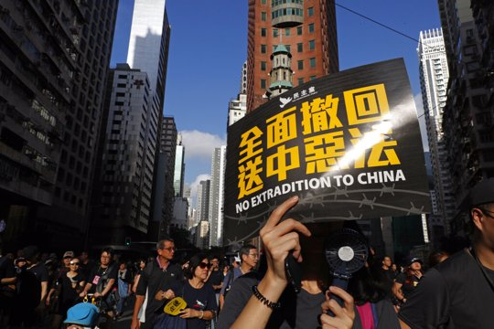 "Protesters march with a card that reads ""Fully withdraw the extradition to China evil law"" in Hong Kong on Sunday, July 21, 2019. Tens of thousands of Hong Kong protesters marched from a public park to call for an independent investigation into police tactics."
