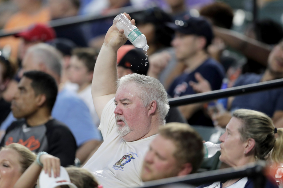 Man Pouring Water Over Head At Baseball Game