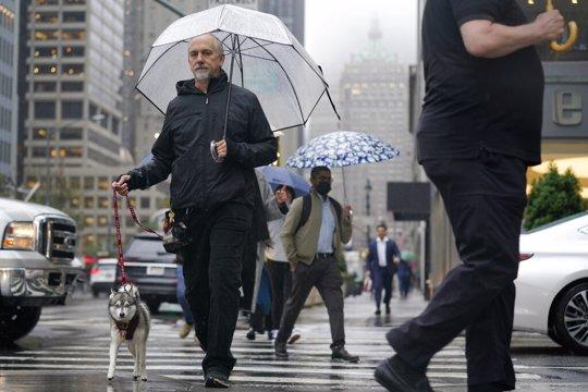 Pedestrians make their way through a rainy and foggy New York