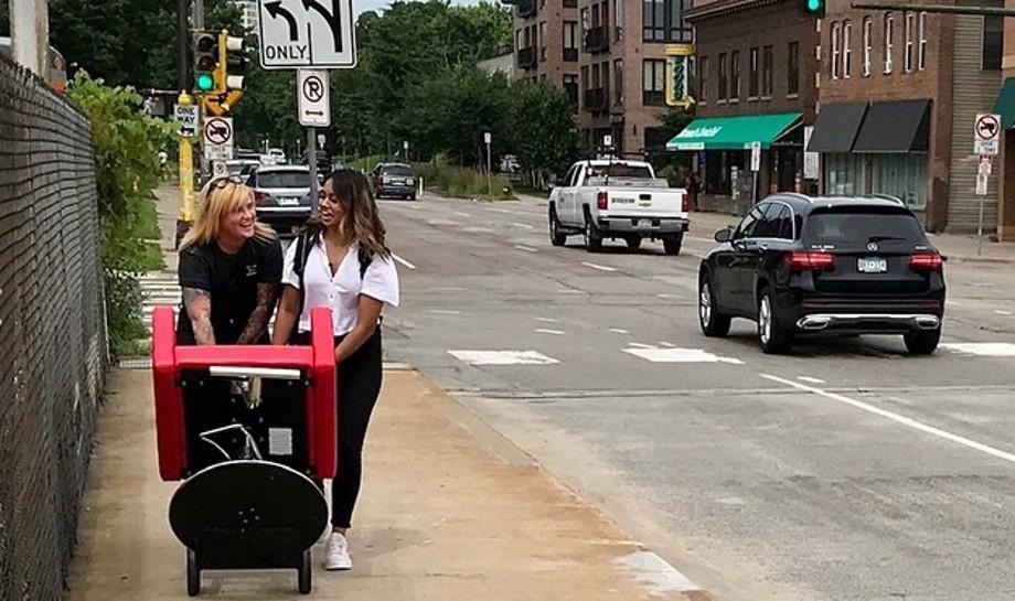 Red salon chair wheeled along sidewalk by two women