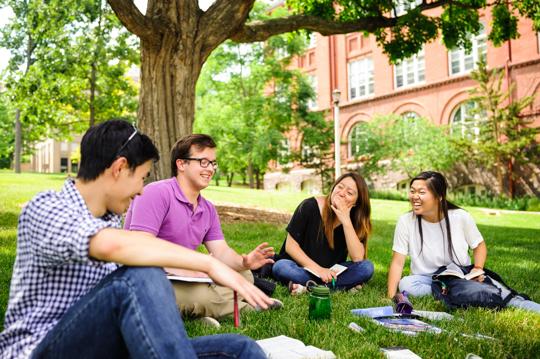 InterVarsity students sitting on college campus lawn