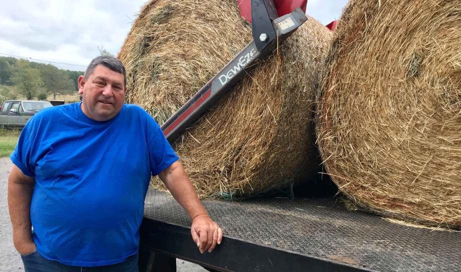 Farmer with hay rolls on truck