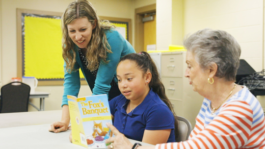 Students, teacher and church volunteer read book