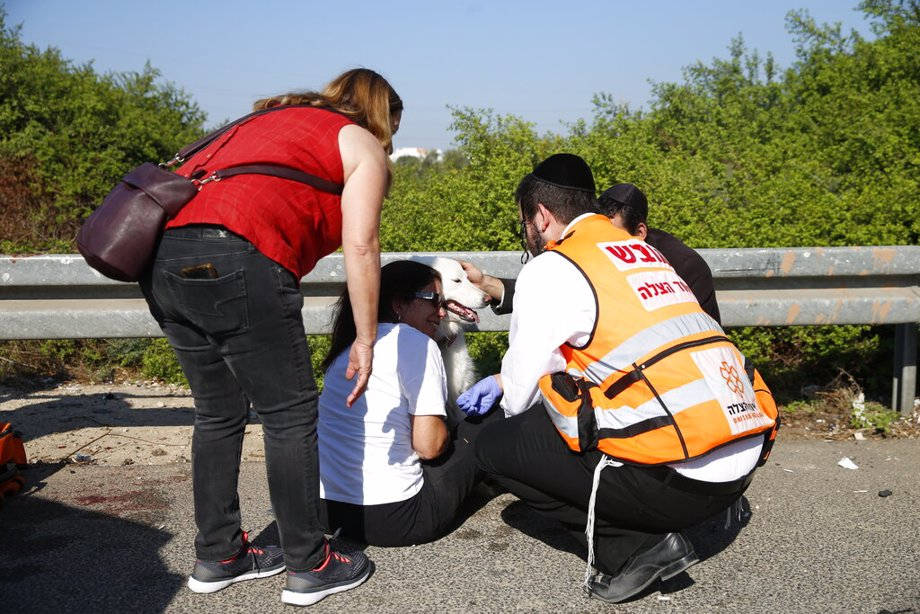 Paramedics treat a woman and her dog moments after a rocket fired by Palestinians militants from Gaza hit a main free way between Ashdod and Tel Aviv