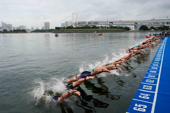 athletes dive into the water at the start line during a women's triathlon test event at Odaiba Marine Park