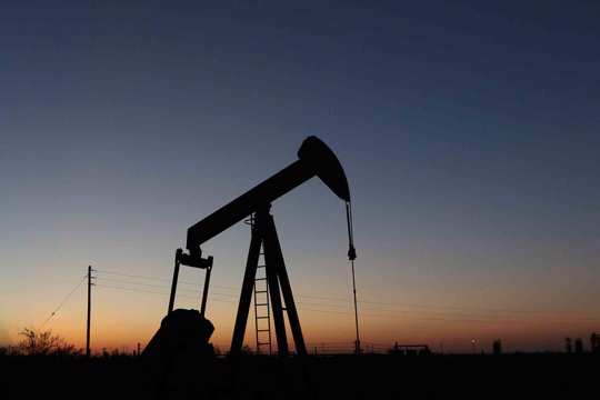 An oil derrick pump jack operates in an oil field in the Permian Basin in Texas