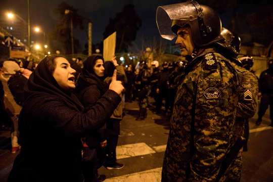 a woman attending a candlelight vigil to remember the victims of the Ukraine plane crash, talks to a policeman, at the gate of Amri Kabir University in Tehran, Iran