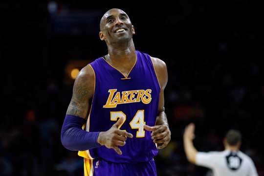 Los Angeles Lakers' Kobe Bryant smiles as he jogs to the bench during the first half of an NBA basketball game against the Philadelphia 76ers in Philadelphia
