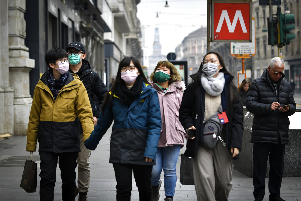 People wear sanitary masks as they walk in downtown Milan, Italy