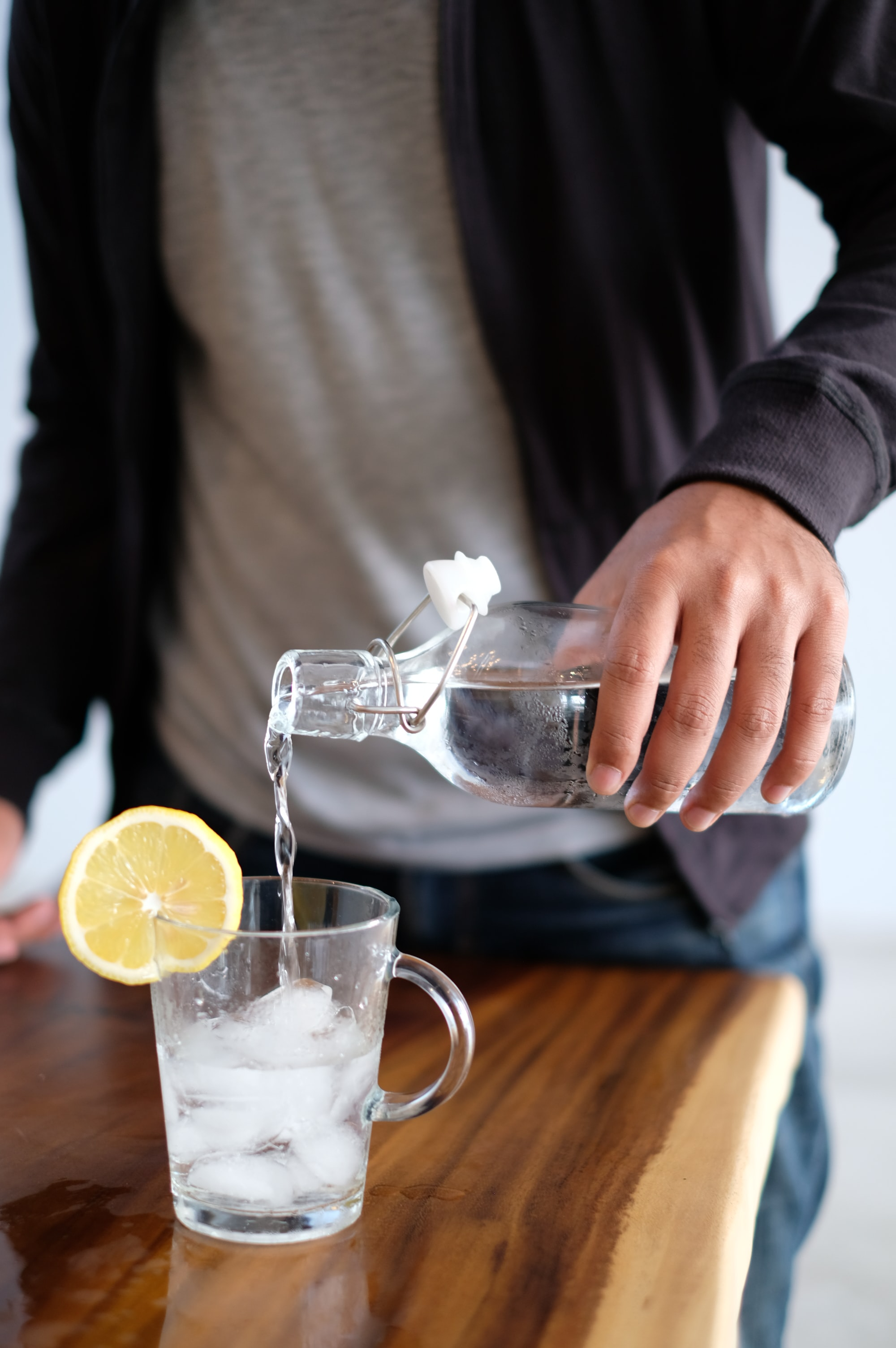 Man pouring water over ice, lemon slice on side