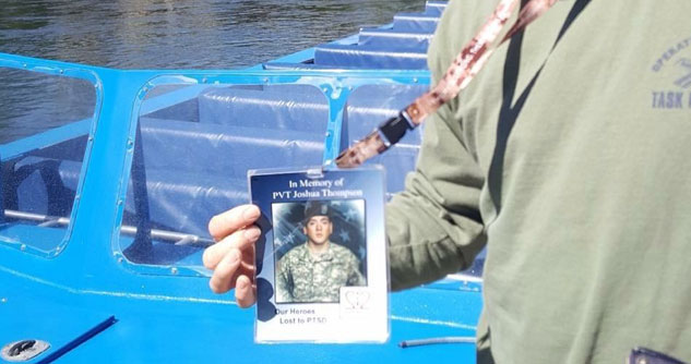 man holding a picture of a fallen service man