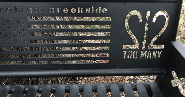 metal bench with Operation Creekside and 22 Too Many and American Flag carved out of bench
