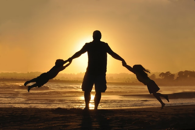 dad swings his daughter and son around on a beach at sunset