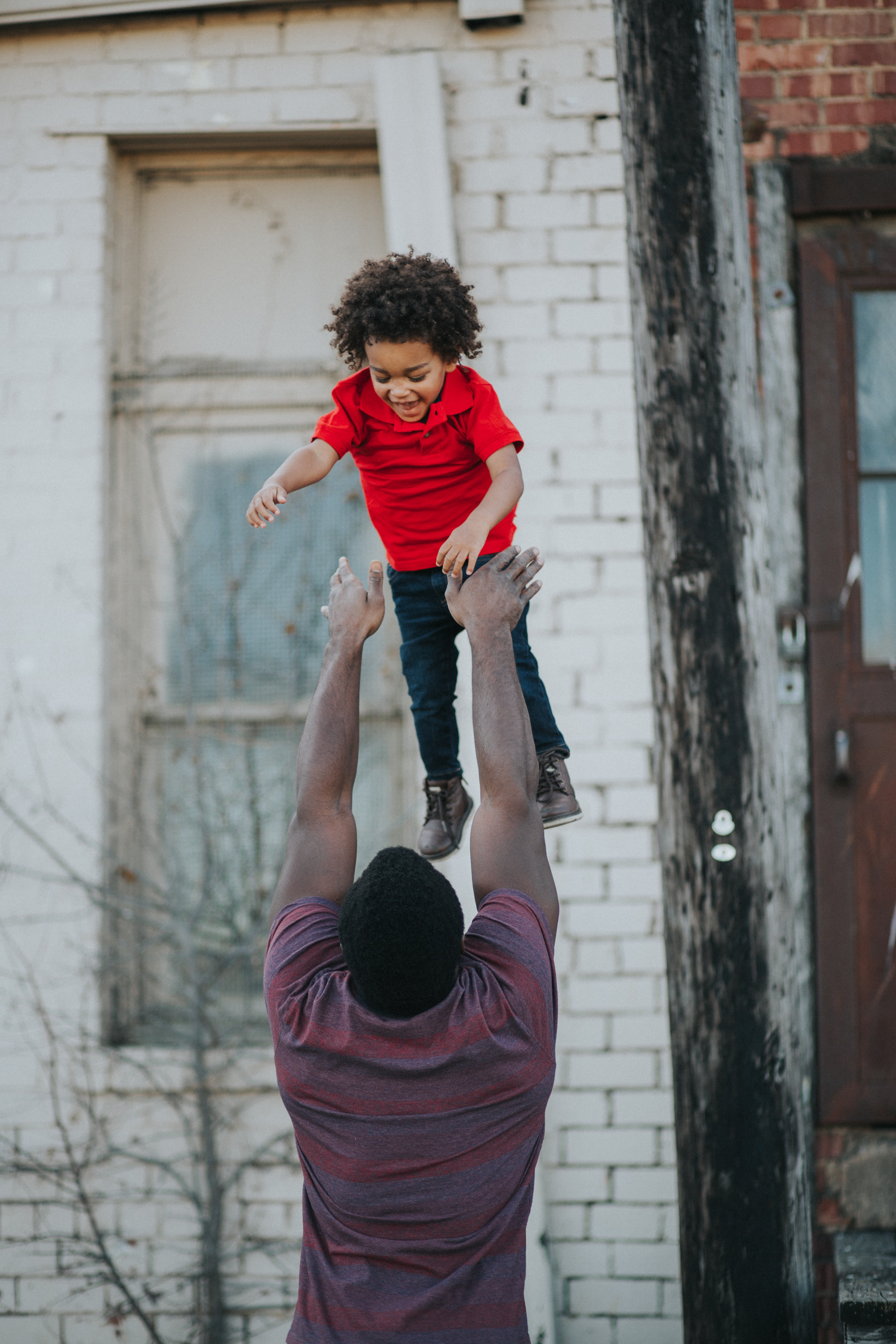 dad tosses his laughing child up in the air