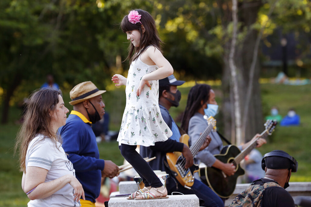 Young girl dances while listening to band in NYC park