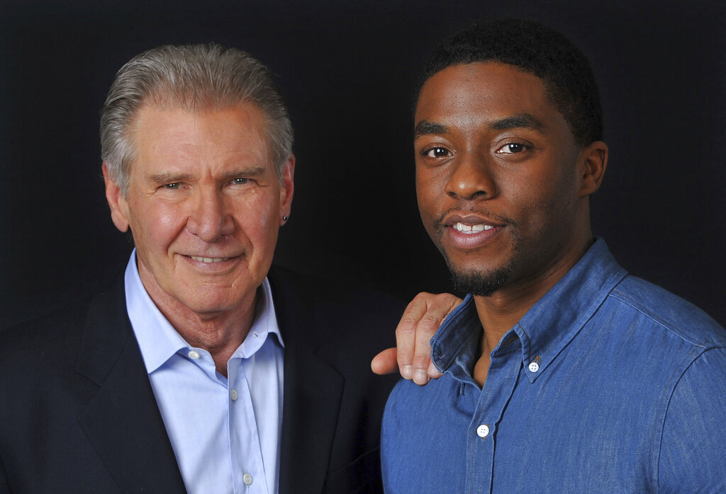"In this Saturday, March 23, 2013 file photo, Harrison Ford, left, and Chadwick Boseman, cast members in the film ""42,"" pose together for a portrait, in Los Angeles. Boseman, who played Black icons Jackie Robinson and James Brown before finding fame as the regal Black Panther in the Marvel cinematic universe, has died of cancer. His representative says Boseman died Friday, Aug. 28, 2020 in Los Angeles after a four-year battle with colon cancer. He was 43."