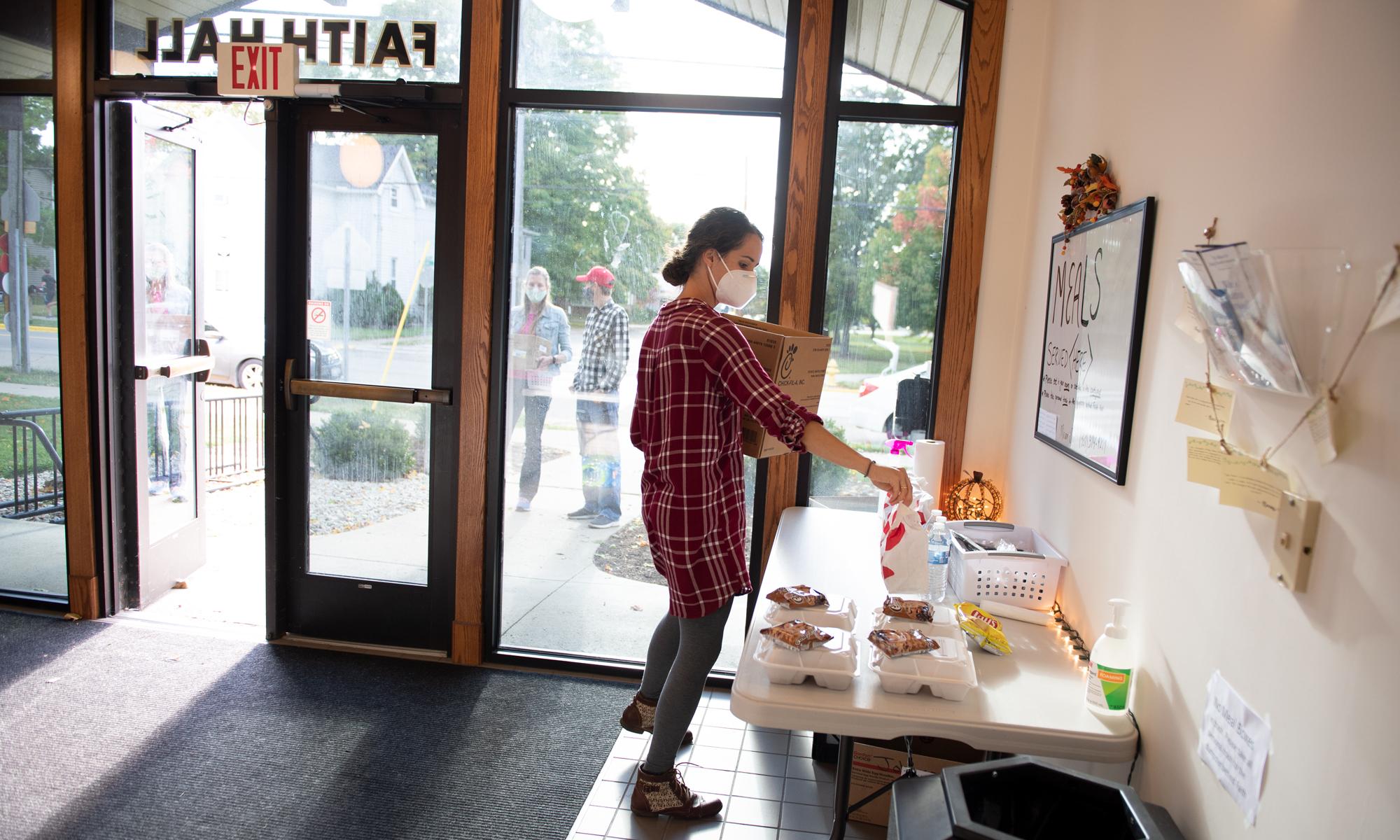 Faith Hall Resident Director Miriam Olar prepares food for students in isolation
