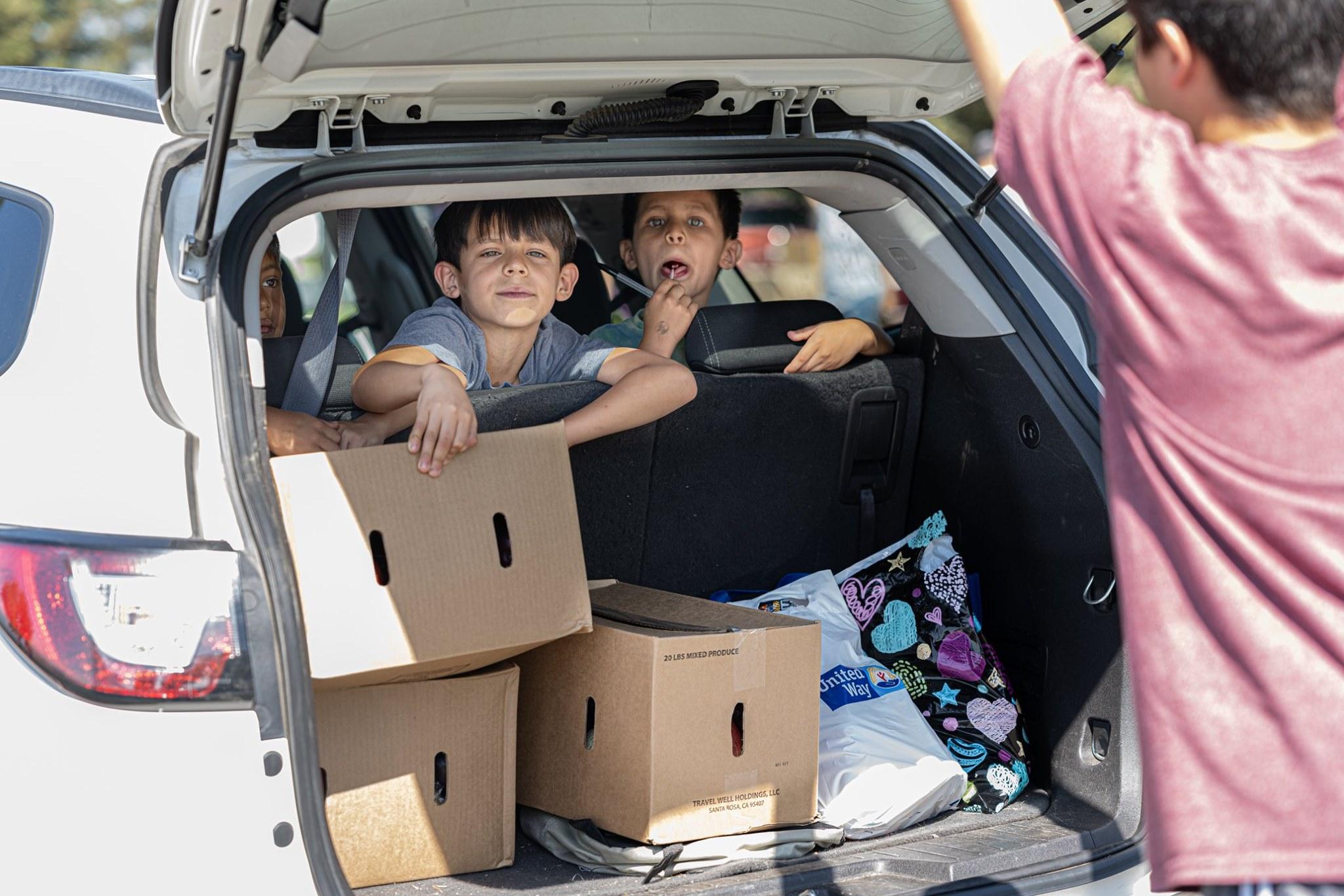 Kids in car receiving food boxes