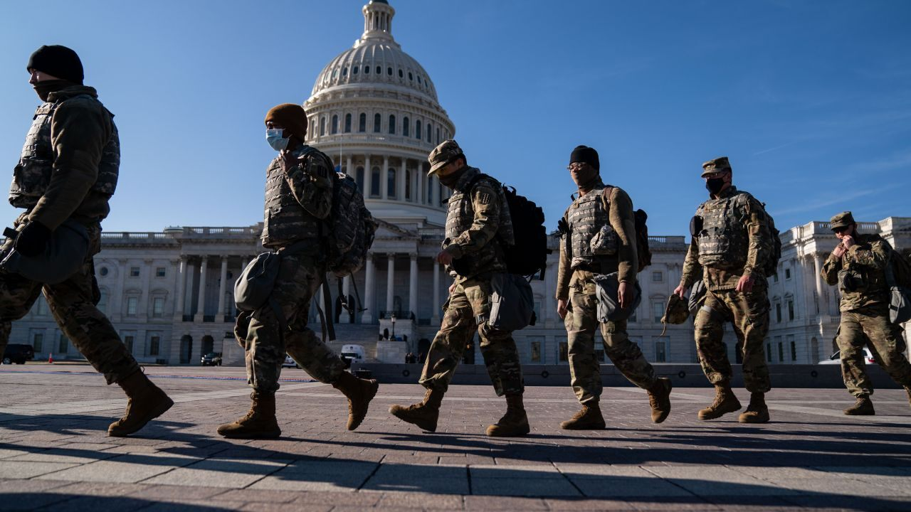 men in uniform marching in front of the US Capitol