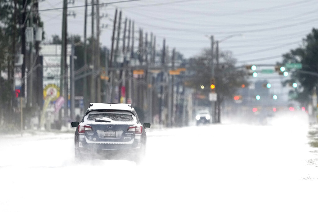 Vehicles drive on snow and sleet covered roads in Spring, Texas