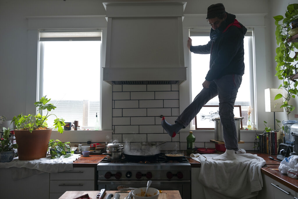Man stands on kitchen counter to warm his feet over gas stove