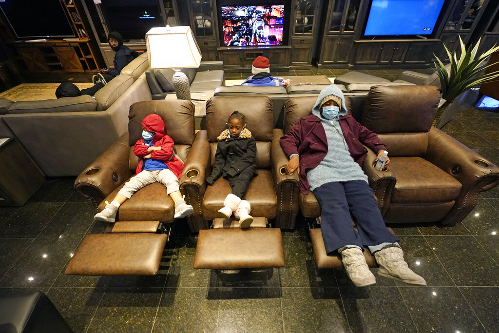 Joecyah Heath, left, Morning Day, center, and Jenesis Heath rest in recliners at a Gallery Furniture store which opened as a shelter in Houston