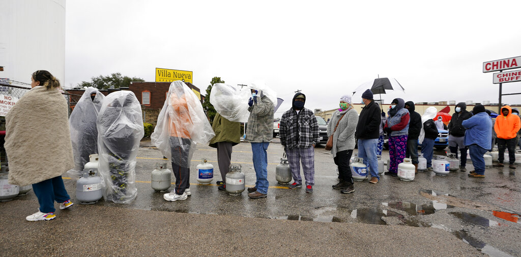 People wait in line to fill propane tanks in Houston. Customers had to wait over an hour in the freezing rain to fill their tanks.