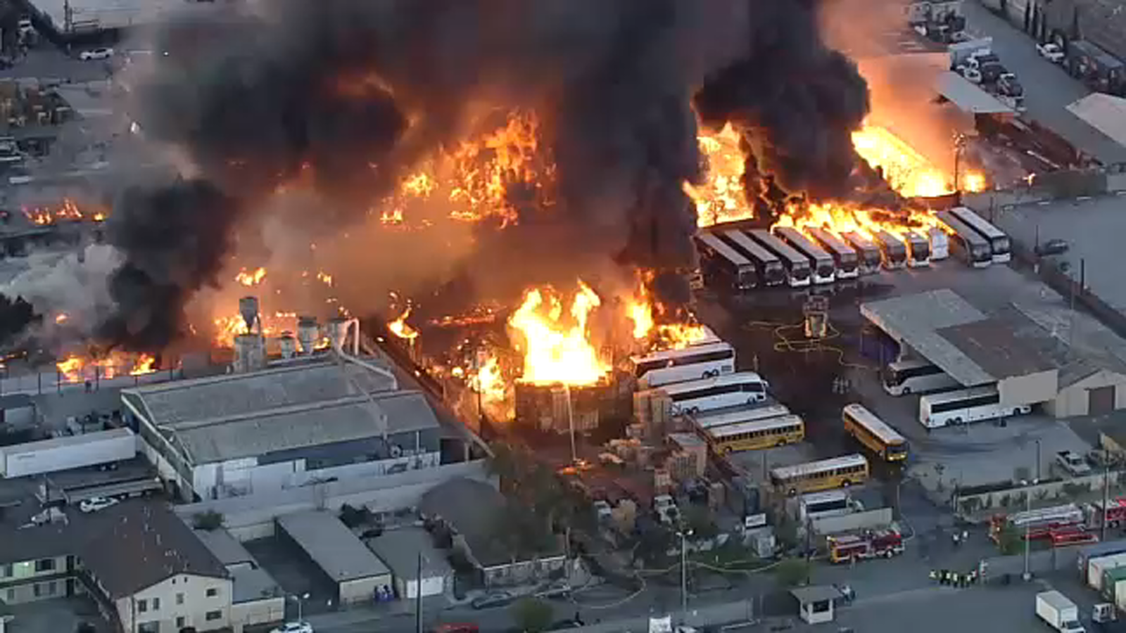 A massive fire in an industrial area of Compton engulfed several structures and buses, sending a thick plume of smoke into the sky Friday morning.