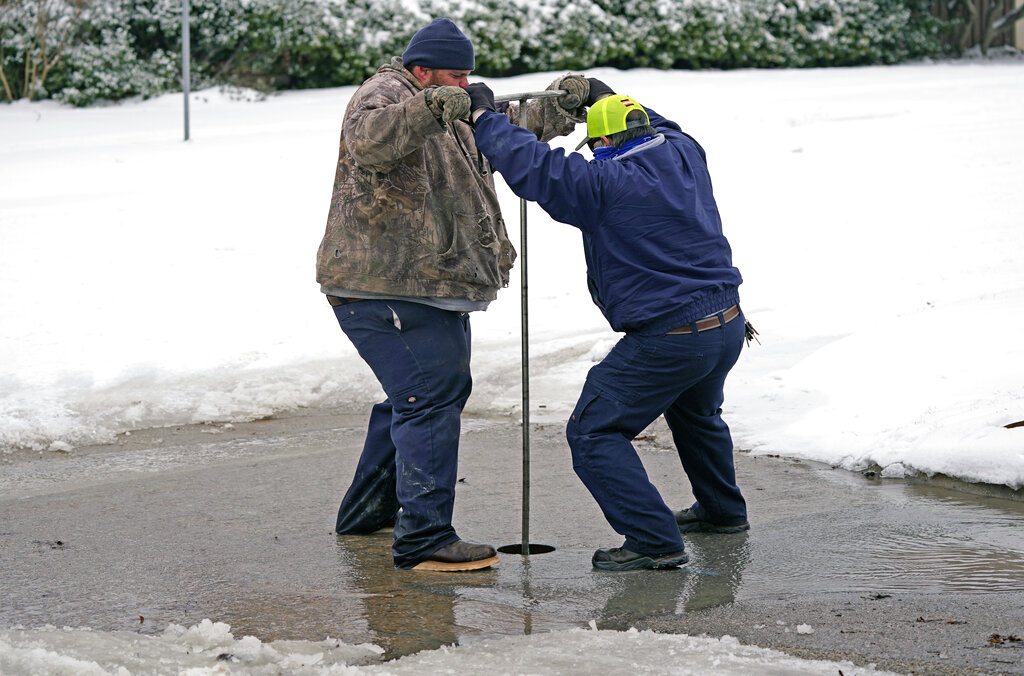 City of Richardson workers close a water main valve for a pipe that burst due to extreme cold