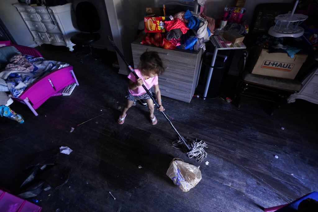 Raella Mills, 3, plays mop-up at her home in Dallas. Raella and her mother