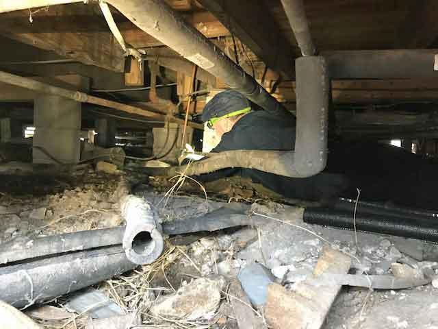Under a home: Plumber Bruce Singleton, Colorado volunteer