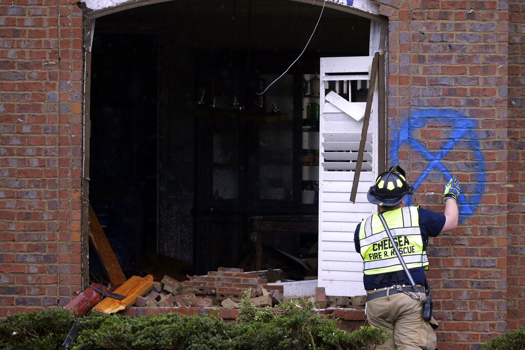 A firefighter marks a house after a tornado touches down south of Birmingham, Ala., in the Eagle Point community