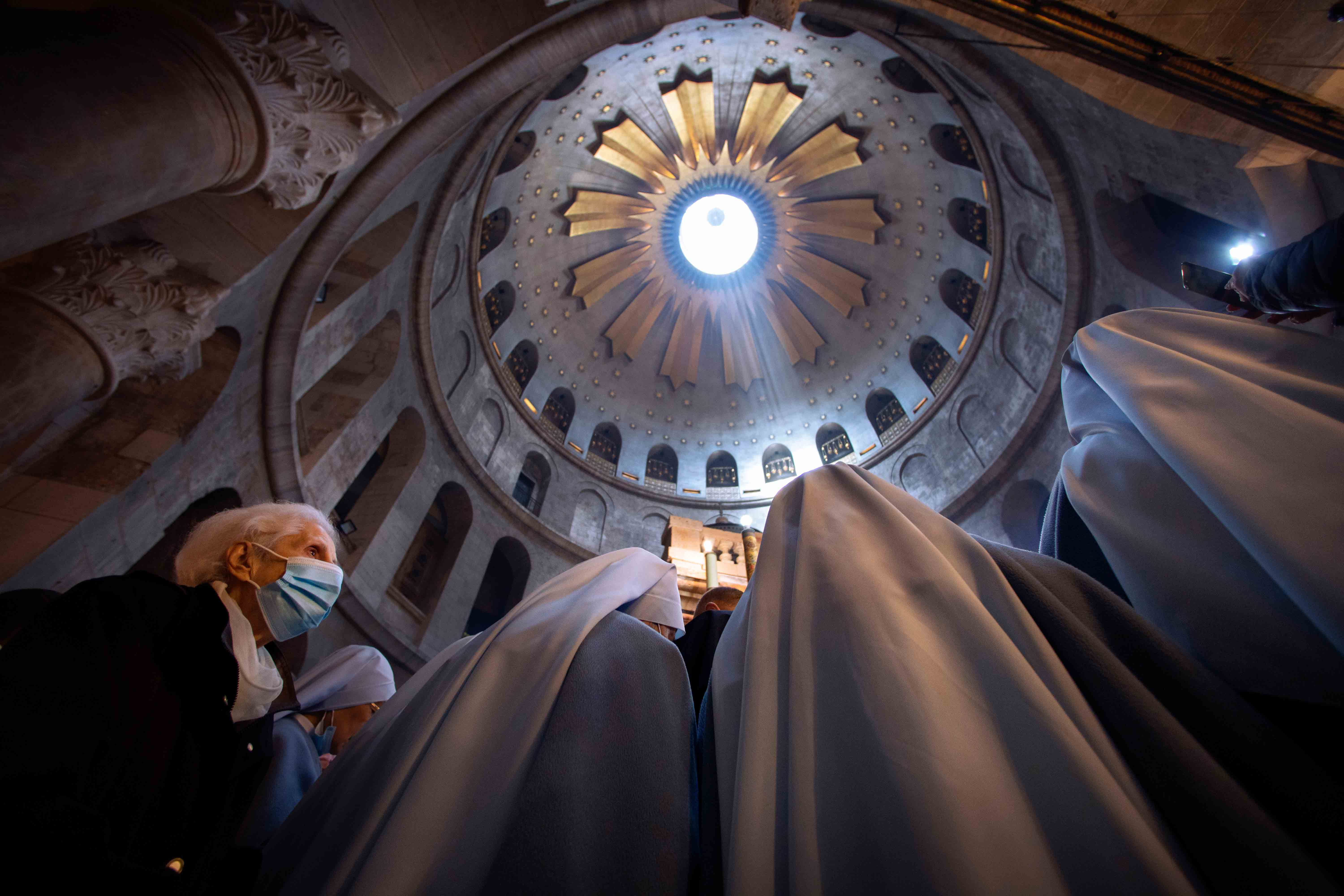 A woman wearing a face mask attends Easter Sunday Mass led by Latin Patriarch of Jerusalem Pierbattista Pizzaballa at the Church of the Holy Sepulchre,  in the Old City of Jerusalem, Sunday, April 4, 2021.
