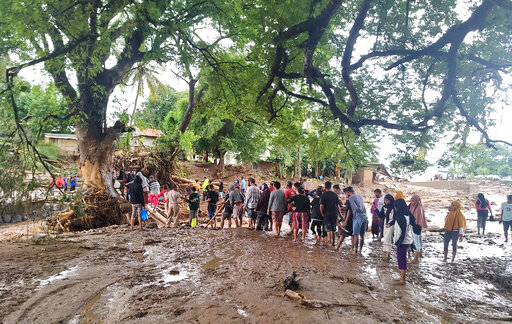 People queue up to cross a makeshift bridge at a village affected by floods on Adonara Island, East Flores, Indonesia
