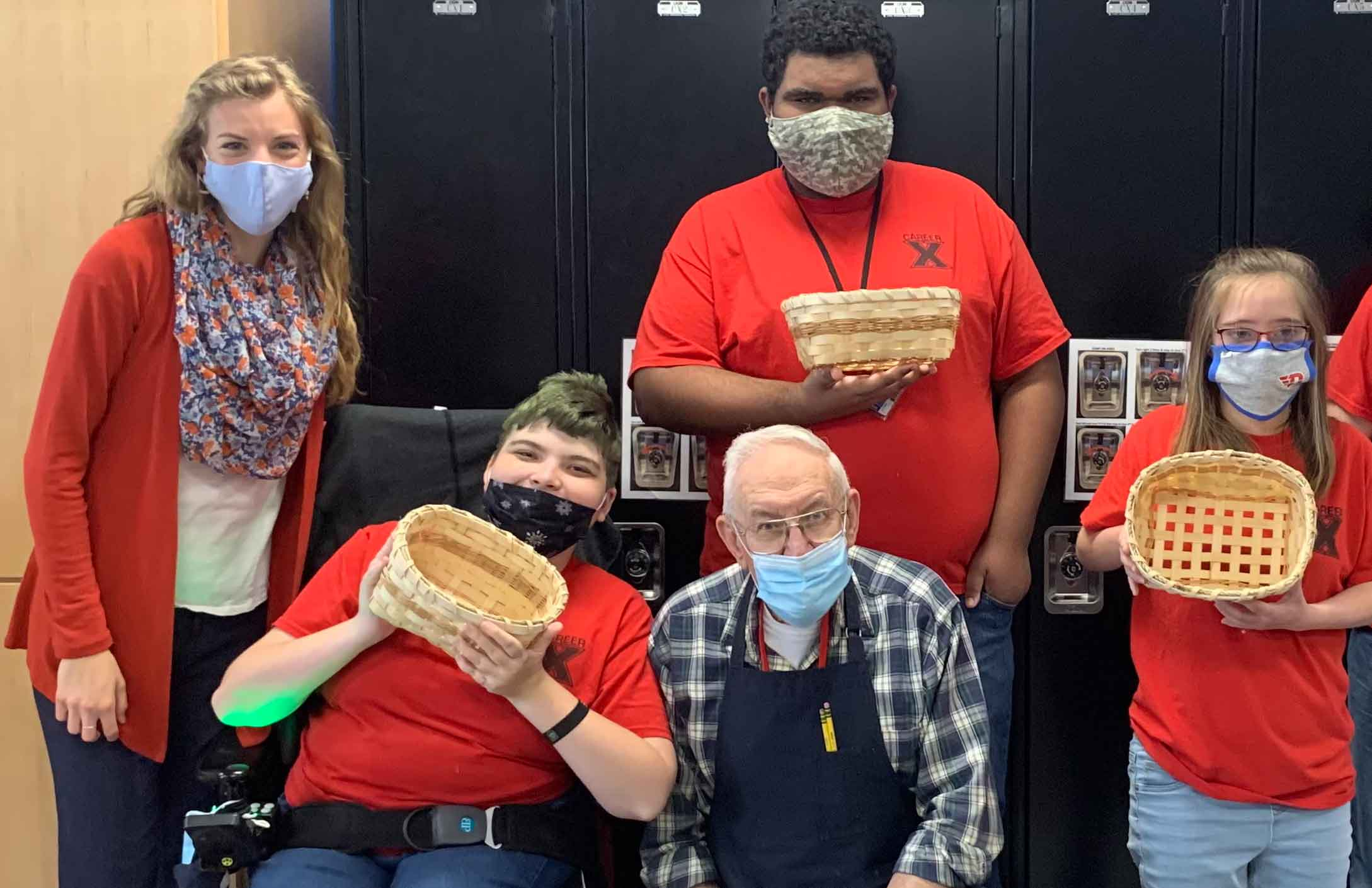 Anna and John smile amongst students who display the baskets they made in John's basket weaving class.