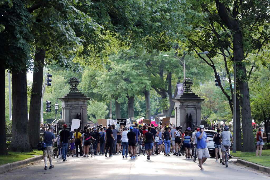 Protesters walk through the gate of a private street not far from the home of Mark and Patricia McCloskey, Friday, July 3, 2020, in St. Louis.