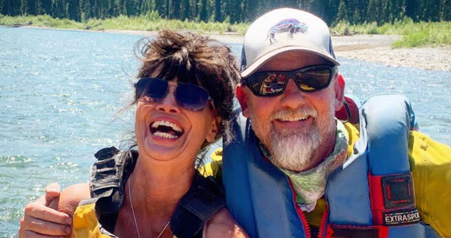 Man and wife with life jackets and sunglasses smiling