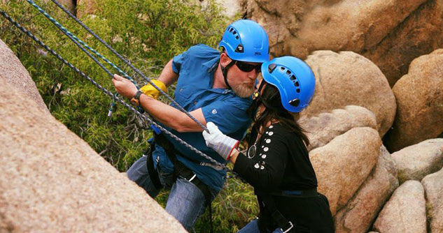 Husband and wife kiss while rock climbing